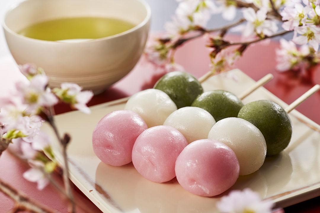 お茶と3色串団子が3本。桜の木々に囲まれている。